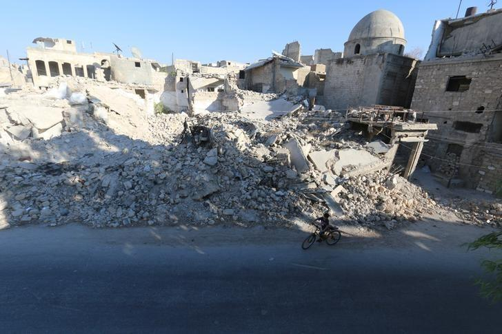 A boy rides a bicycle near rubble of damaged buildings in the rebel held al-Maadi district of Aleppo