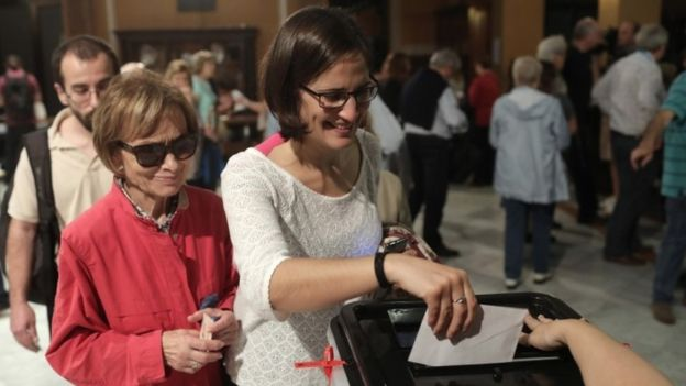 A voter casts a ballot in the Catalan independence referendum