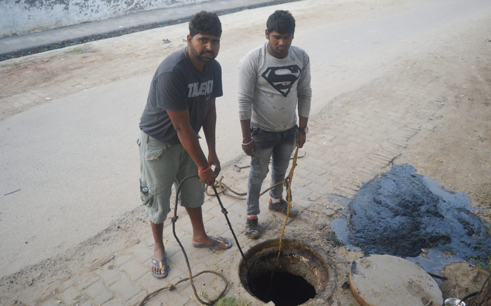 Sanitation workers in India prepare a to clean a sewer.