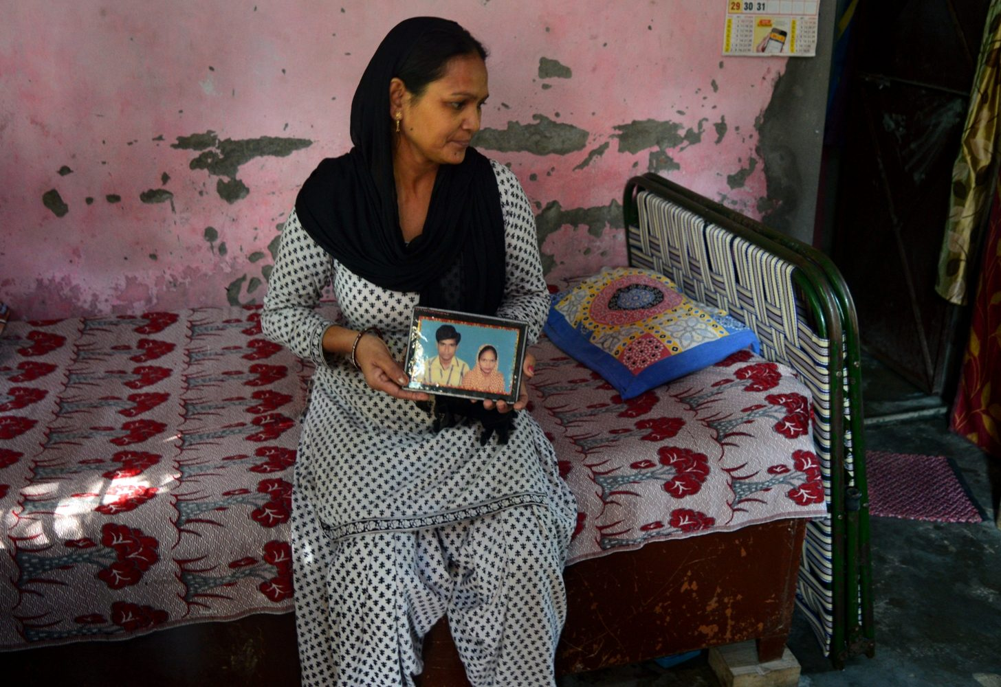 A woman in India shows a photo of her husband who died while working as a manual sewage cleaner.