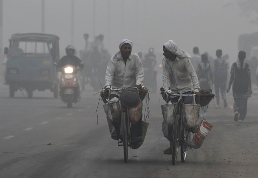 Commuters in India cycle through heavy smog