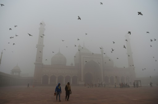 People walk through the smog in the old quarters of New Delhi