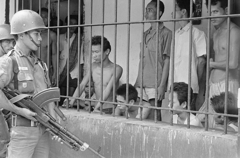 An Indonesian soldier guards suspected Communists outside of Jakarta in 1965 massacre Indonesia human rights