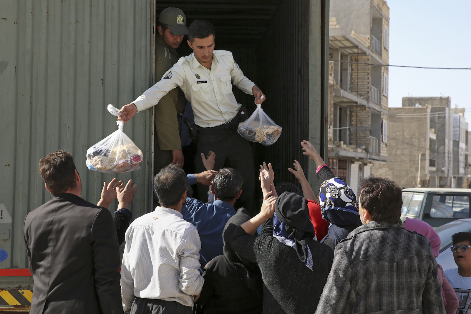 A police officer gives supplies to survivors of the earthquake in Iran