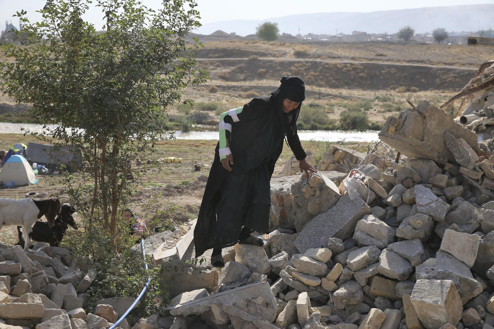 A survivor of the earthquake in Iran climbs over rubble