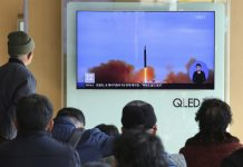 People watch a TV with footage of a missile test in North Korea