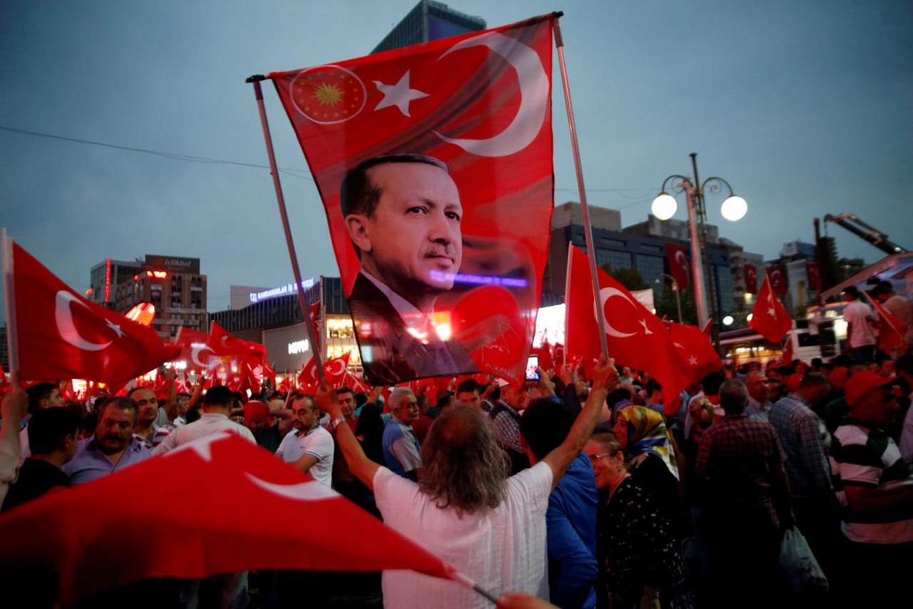 A supporter holds a flag depicting Turkish President Tayyip Erdogan during a pro-government demonstration in Ankara
