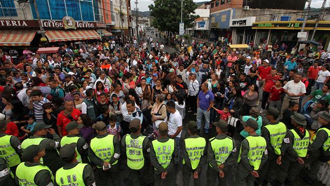 Venezuelans wait for their turn to cross into Colombia,
