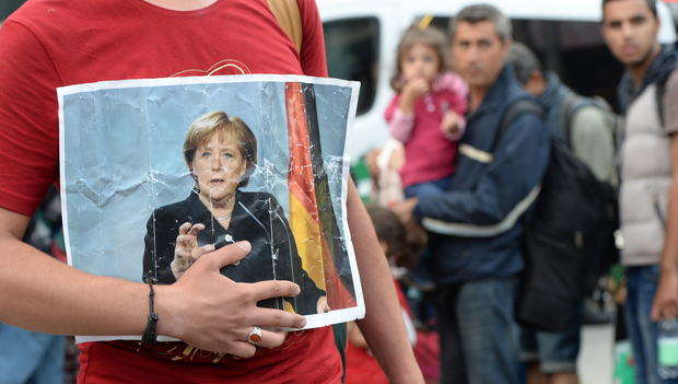 A refugee holds a picture of German Chancellor Angela Merkel