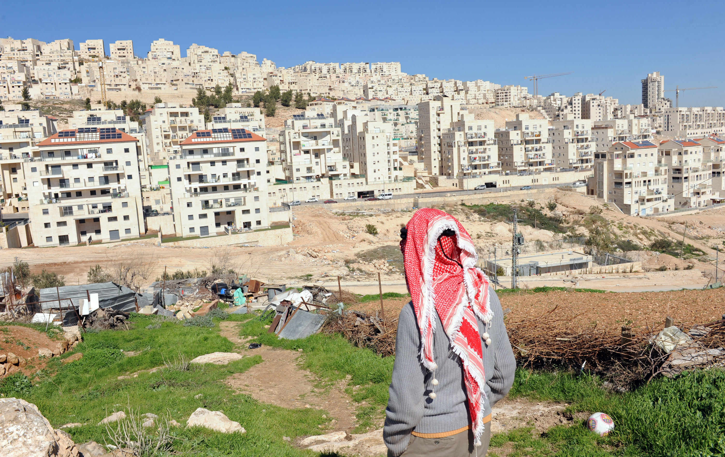 A Palestinian looks at the Israeli settlement Har Homa in the West Bank