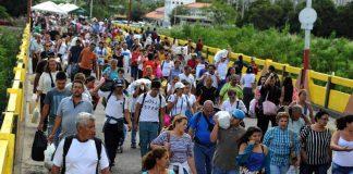 Venezuelans carrying groceries cross a bridge from Colombia back to Venezuela