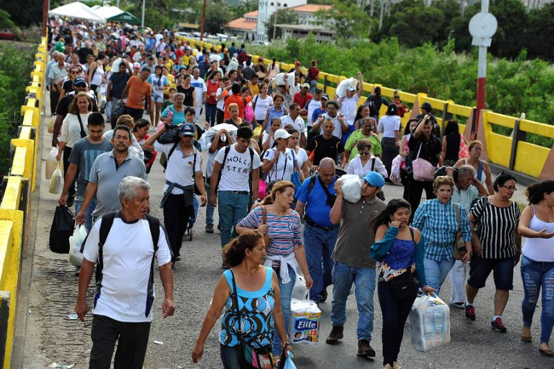Venezuelans carrying groceries cross a bridge from Colombia back to Venezuela
