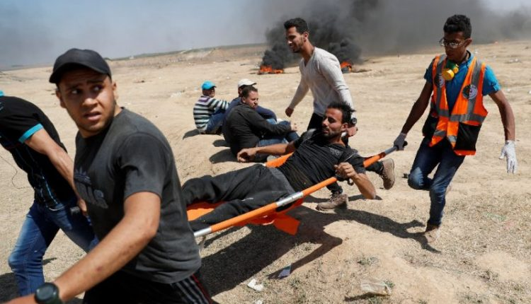 A wounded Palestinian is being carried away on a stretcher by four men, while smoke appears in the background.