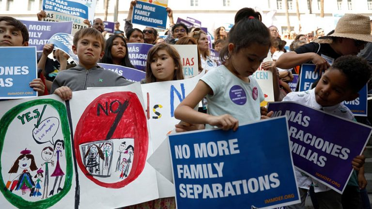 People hold signs to protest against the separation of families at the US-Mexico border.