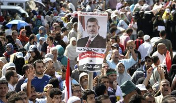 Supporters of Muslim Brotherhood President Mohamed Morsi, hold his posters as they rally at the Rabaa Adawia square where they are camping.