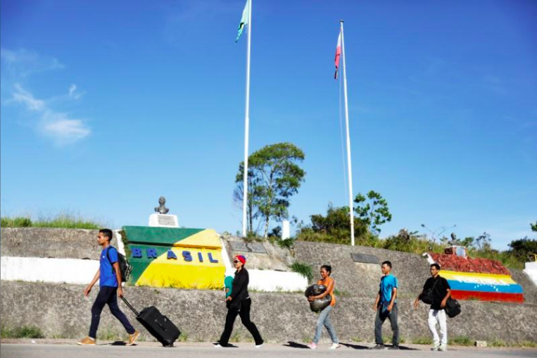 Venezuelans walk across the border from Venezuela into the Brazilian city of Pacaraima, Roraima state, Brazil.