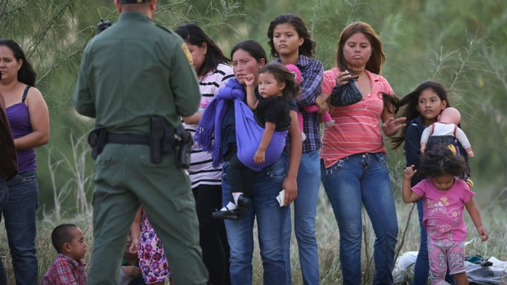 Migrant women and children with a US border patrol officer