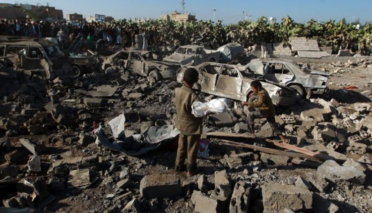 Yemenis stand at the site of a Saudi air strike against Huthi rebels near Sanaa Airport in March, 2015