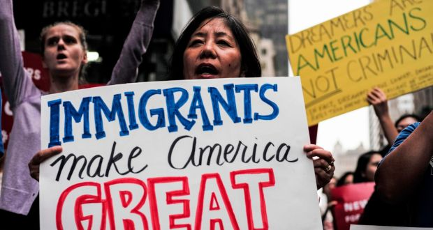 "A woman displays a sign that reads ""immigrants make America great"" during a demonstration against US President Donald Trump during a rally in support of the Deferred Action for Childhood Arrivals (DACA), near the Trump Tower in New York in 2017."