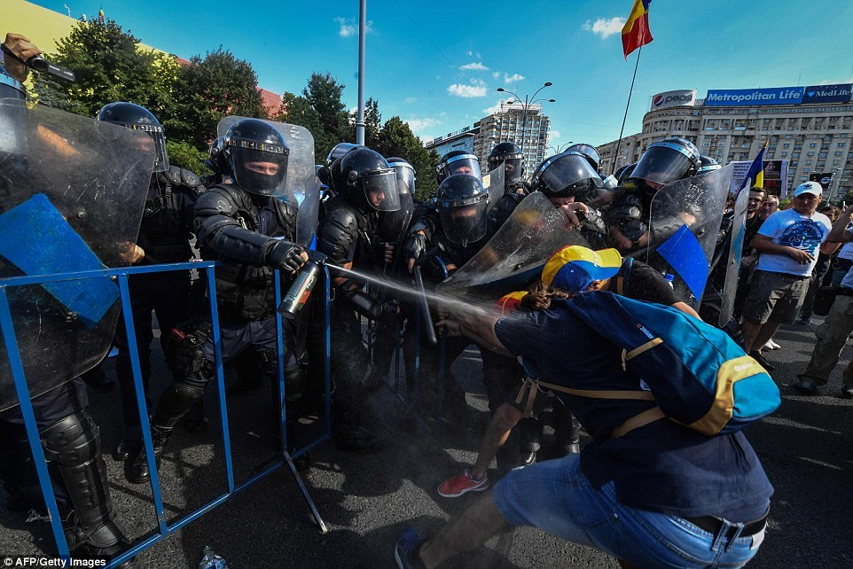 Riot police spray tear gas while scuffling with protesters outside the government headquarters in Bucharest, Romania