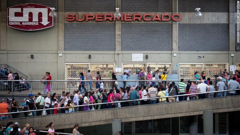 People queue up outside a supermarket in Caracas, Venezuela