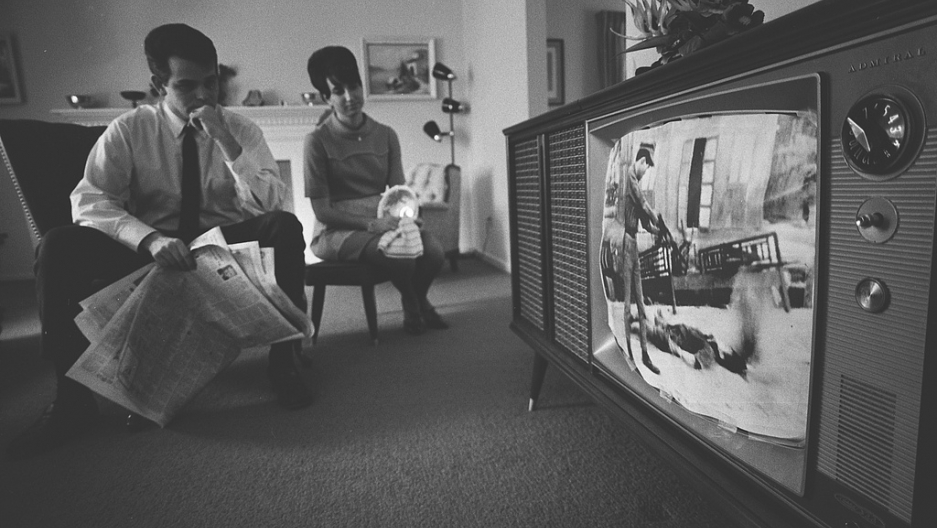 A couple watching footage of the Vietnam War on their television, February, 1968.