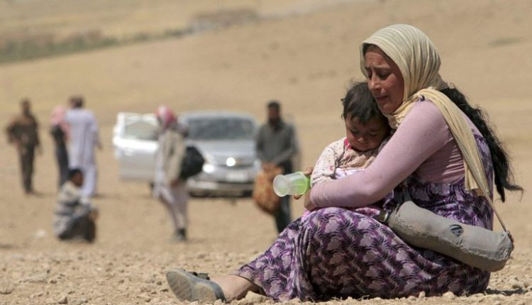 A displaced Yazidi woman and child flee violence from Islamic State in Sinjar, Iraq