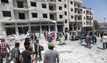 Syrians at a site of car bomb in Idlib