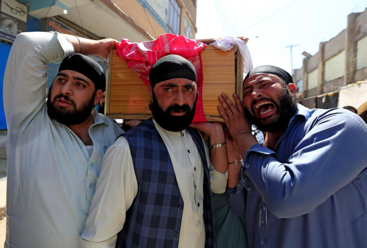 Afghan Sikh men carry the coffin of one of the victims of yesterday's blast in Jalalabad city, Afghanistan July 2, 2018