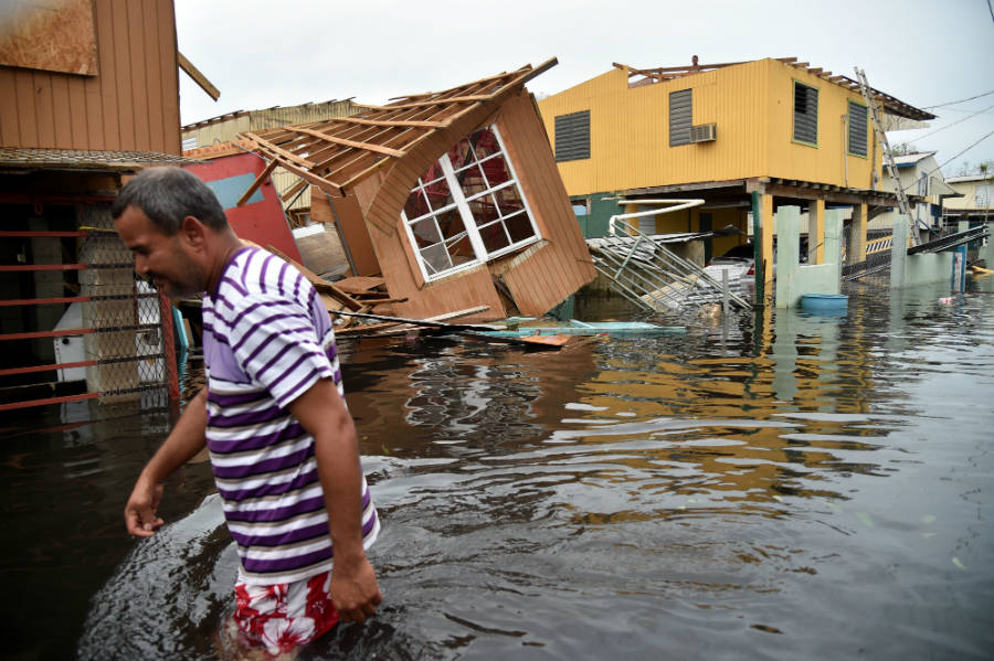 A men walks down a flooded street, where houses have collapsed, after Hurricane Maria had hit the island of Puerto Rico