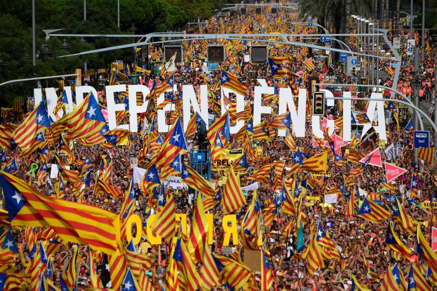 People wave pro-independence Catalan flags 'Esteladas' while holding letters reading 'independence' during a pro-independence demonstration in Barcelona, Spain