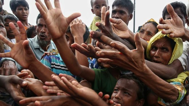 Rohingya refugees reaching for food aid at Kutupalong refugee camp in Bangladesh