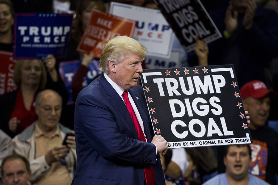 US President Donald Trump displays a sign saying 'Trump digs coal' during a rally.