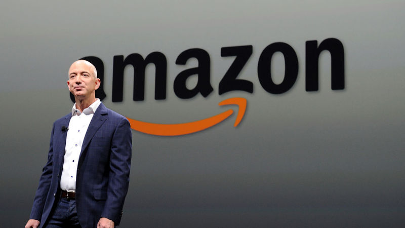 Jeff Bezos standing next to an Amazon sign