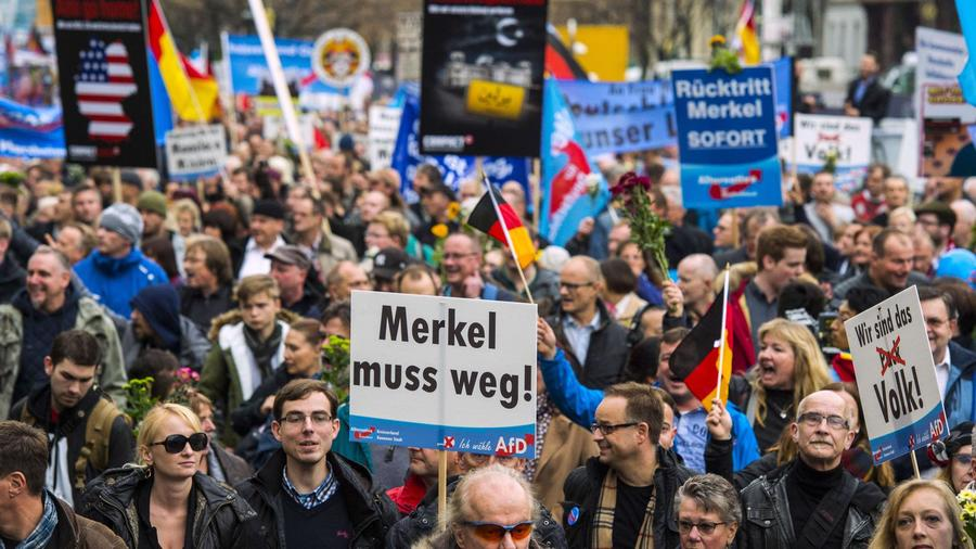 Supporters of Germany's AfD show German flags and display posters saying 'Merkel must go'