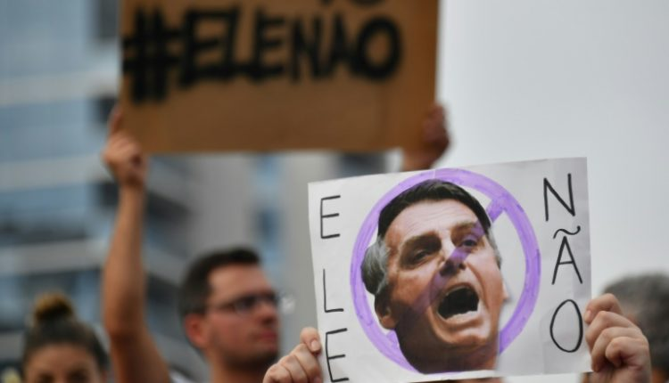 Protesters displaying signs with far-right president-elect Jair Bolsonaro's face reading #EneNao (not him)