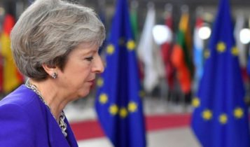 British Prime Minister Theresa May in front of flags of the European Union (EU)