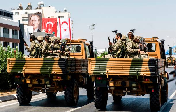 Turkish soldiers ride in army vehicles past flags of Turkey and the self-proclaimed Turkish Republic of Northern Cyprus (TRNC) during an army parade in the northern part of Nicosia on July 20, 2017 to mark the 43rd anniversary of the Turkish invasion of northern Cyprus in 1974