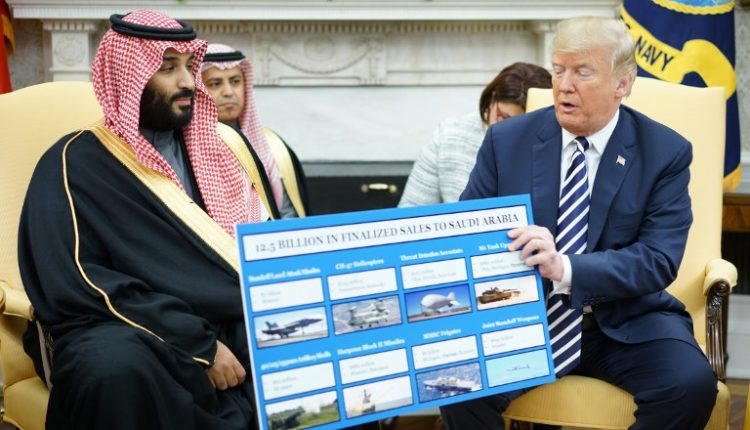 US President Donald Trump (R) holds a defense sales chart with Saudi Arabia's Crown Prince Mohammed bin Salman in the Oval Office of the White House on March 20, 2018 in Washington, DC