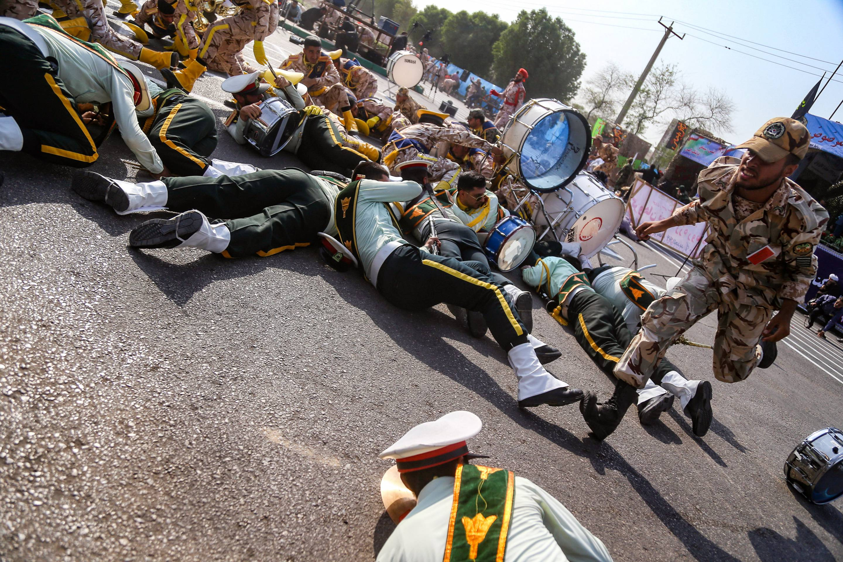 Soldier running past injured comrades lying on the ground at the scene of an attack on a military parade in the Iranian city of Ahvaz on September 22.