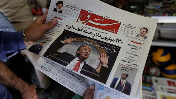 A man looks at a newspaper with a picture of President Trump on the front page, in Tehran, Iran