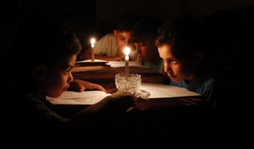 Palestinian children at home reading books by candle light due to electricity shortages in Gaza City.
