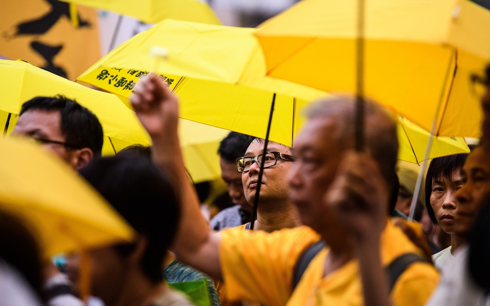 Activists use yellow umbrellas during a gathering outside the Hong Kong government headquarters to mark the fourth anniversary of mass pro-democracy rallies, known as the Umbrella Movement