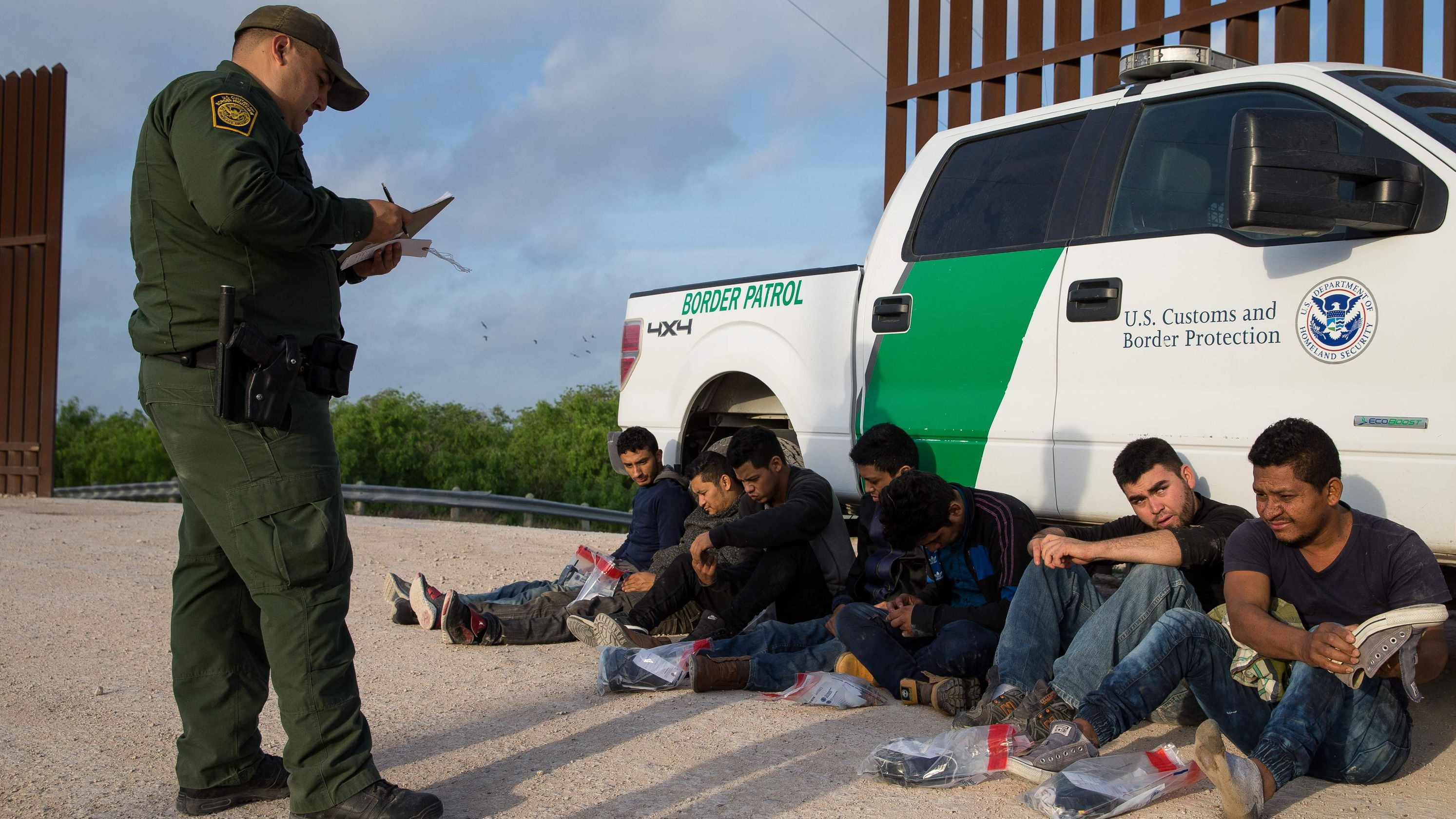 Border Patrol agent apprehends illegal immigrants shortly after they crossed the border from Mexico into the United States in the Rio Grande Valley Sector near McAllen, Texas.