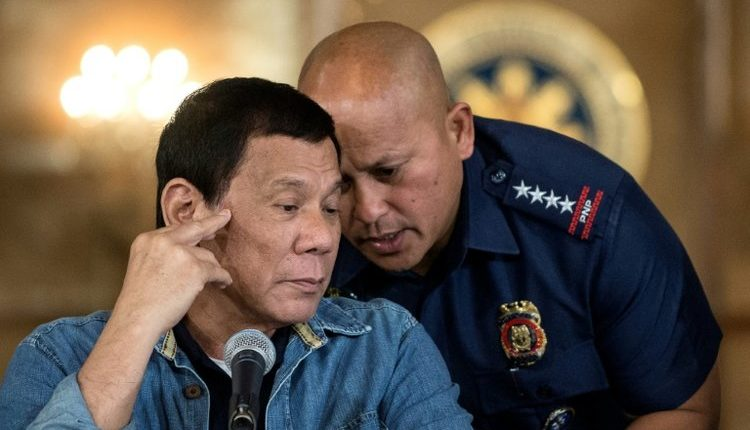 Philippine President Rodrigo Duterte, left, talks to Philippine National Police (PNP) Director General Ronald Dela Rosa, right, during a press conference in Manila on January 30, 2017.
