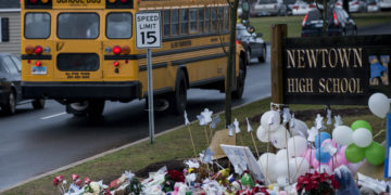 A school bus passes a makeshift memorial to the victims of the Sandy Hook Elementary School shooting as it takes students to Newtown High School December 18, 2012 in Newtown, Connecticut.