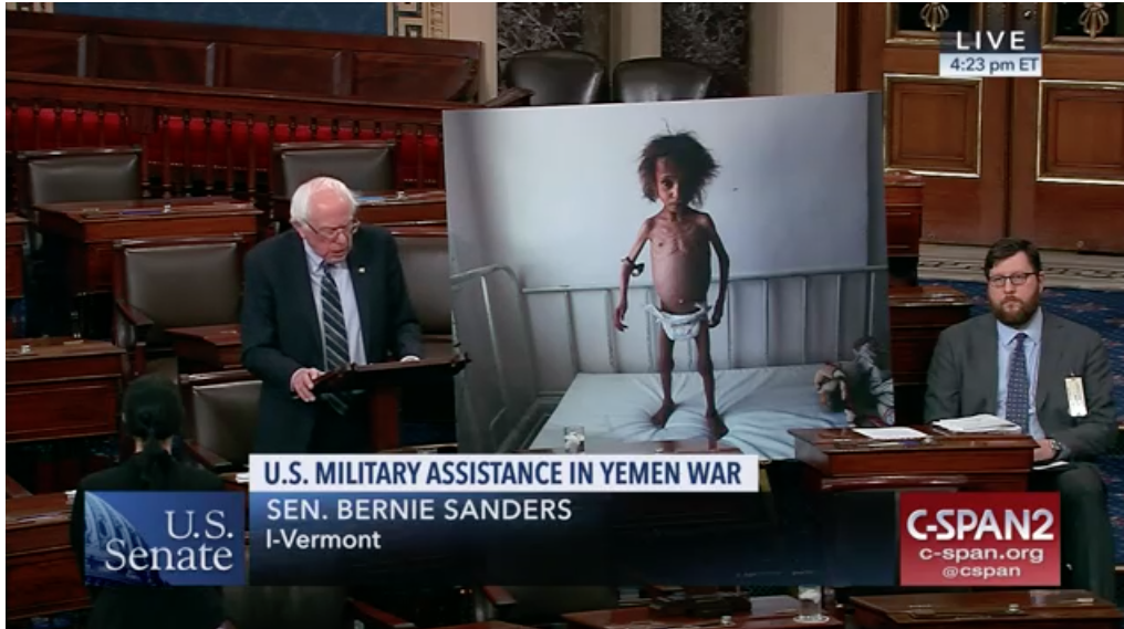Senator Bernie Sanders urges his colleagues to support his Yemen resolution in front of an enlarged photo of a malnourished Yemeni child.