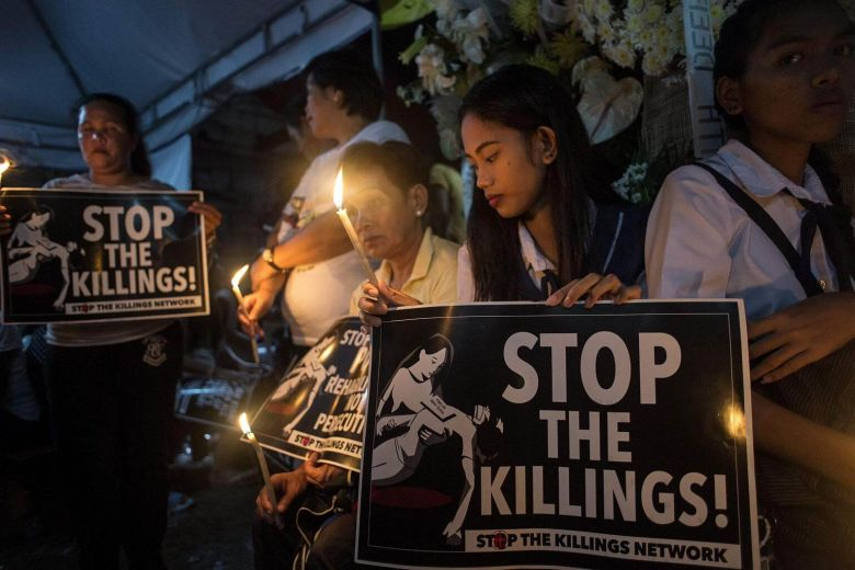 Classmates of 17-year-old student Kian Delos Santos, who was killed allegedly by police officers during an anti-drug raid, light candles at Kian's wake in Manila on Aug 25, 2017.