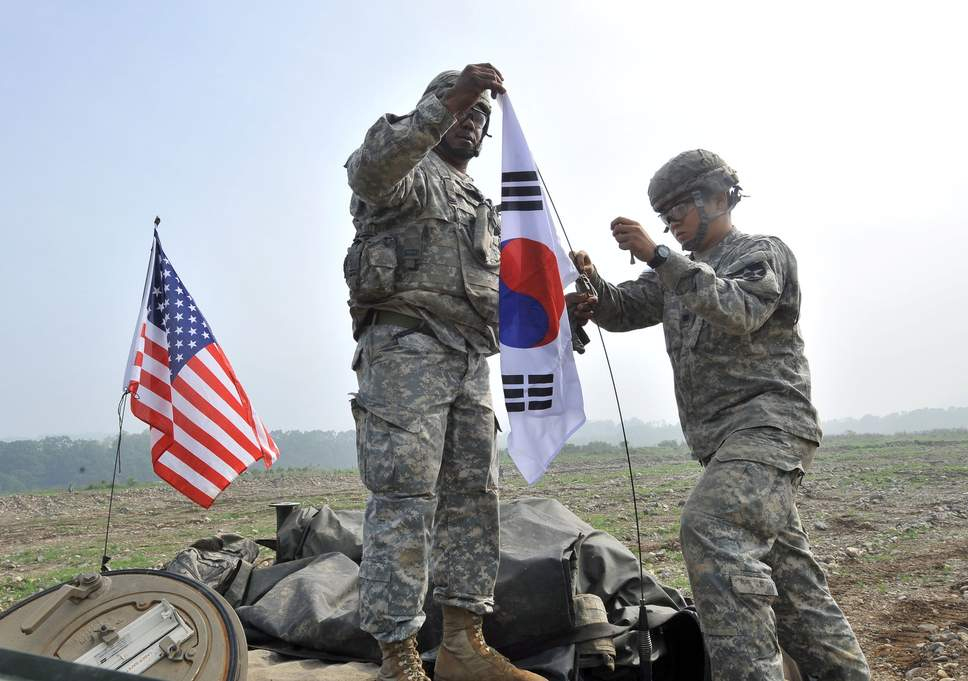 Two soldiers with a US flag and a South Korean flag.