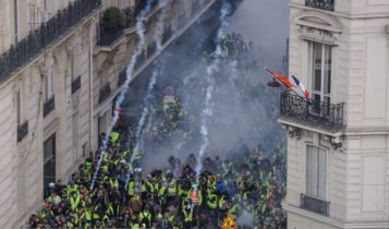 "Shouts of ""Macron, resign"" mingled with the tear gas near the Champs-Elysees avenue in Paris during yellow vests protests"